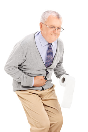 Senior with stomach ache holding toilet paper isolated on white background photo