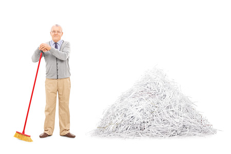 pile of paper: Senior standing by a pile of shredded paper with a broom isolated on white background