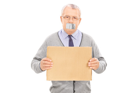 taped: Senior with duct taped mouth holding a blank sign isolated on white background Stock Photo