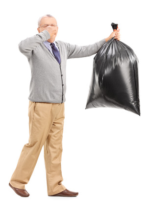 Full length portrait of a senior carrying a stinky garbage bag isolated on white background photo