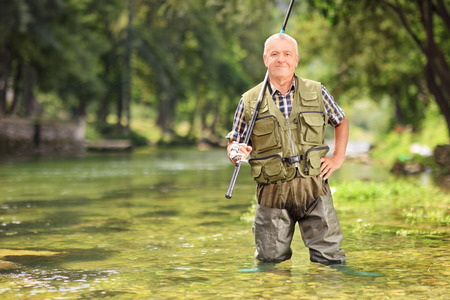 Mature fisherman posing with fishing rod in river, outdoors