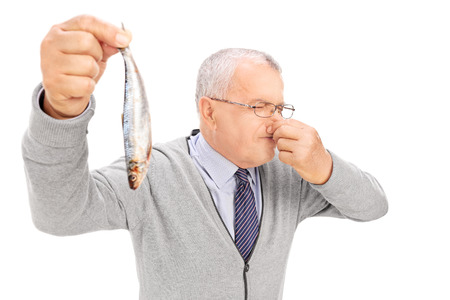Senior gentleman holding a rotten fish isolated on white background