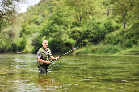 Senior man fishing in a river on a sunny summer day Stock Photo