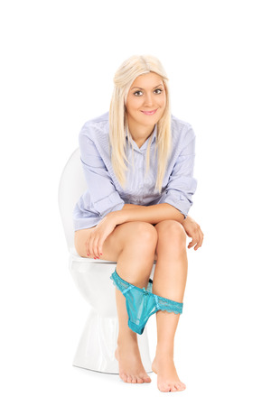 Blond girl peeing seated on a toilet with her panties down isolated on white background