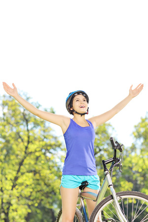Happy female biker posing with raised hands on a mountain bike outdoors photo