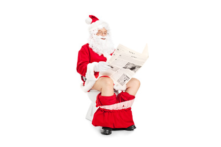 Santa Claus reading a newspaper seated on toilet isolated on white background photo