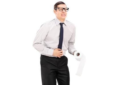 diarrea: Hombre con dolor de estómago celebración rollo de papel higiénico aisladas sobre fondo blanco