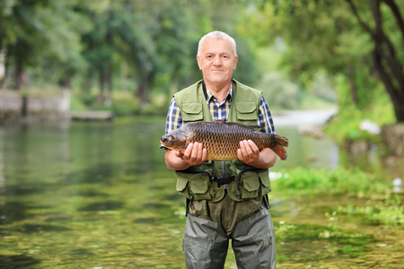 fishing catches: Mature fisherman standing in river and holding a fish outdoors