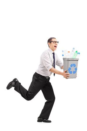 papelera de reciclaje: Hombre alegre que se ejecuta con una papelera de reciclaje en sus manos aisladas sobre fondo blanco