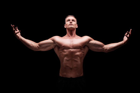 Muscular man gesturing with hands and looking up on black background photo