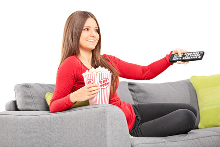 Woman holding a remote control and eating popcorn seated on a sofa isolated on white background photo