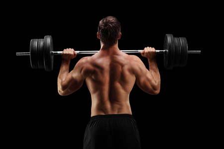 Rear view studio shot of a bodybuilder lifting a barbell on black background