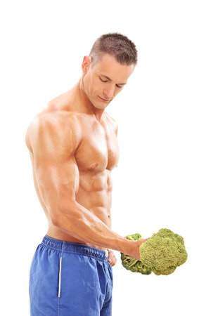 muscle guy: Male bodybuilder exercising with a broccoli dumbbell symbolizing healthy nutrition isolated on white background