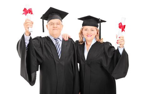 graduacion de universidad: Pareja mayor celebración de sus diplomas aislado en fondo blanco Foto de archivo