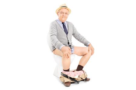 Studio shot van een gelukkige senior zit op een toilet op een witte achtergrond