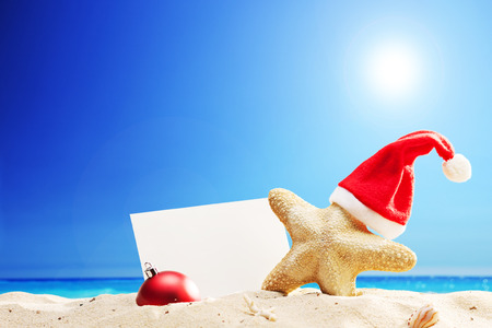 Starfish with Santa hat and a blank paper stuck on a beach on sunny summer day photo