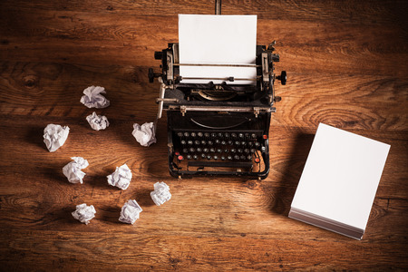 Retro typewriter on a wooden desk and a stack of paper beside it 스톡 콘텐츠
