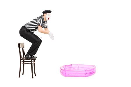 pantomima: Mimo saltando en una pequeña piscina inflable aislado en fondo blanco