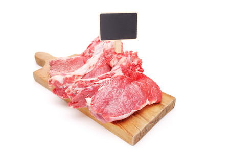 price cutting: Studio shot of raw beefsteaks on a cutting board with a price tag isolated on white background