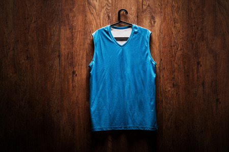 dressing room: Blue basketball jersey hanging on a wooden wall on a hanger
