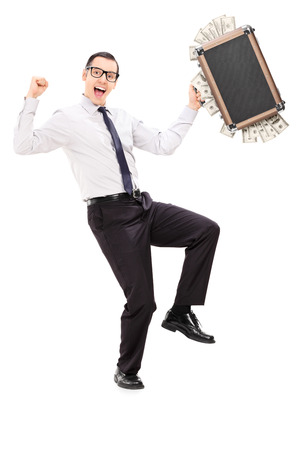 Full length portrait of an overjoyed businessman holding a briefcase full of money isolated on white background photo