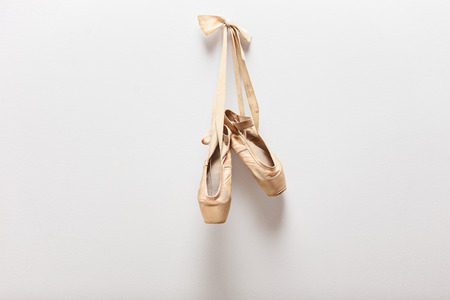 Pair of old silky ballet shoes hanging on a wall Stock Photo