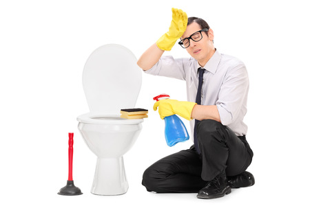 Man cleaning: Exhausted young man cleaning a toilet isolated on white background