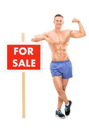 hoer: Volledige lengte portret van een knappe man die door een te koop bord op een witte achtergrond