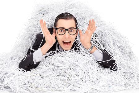 paper shredder: Terrified man covered in a pile of shredder paper isolated on white background