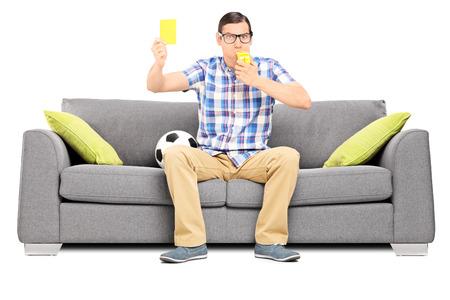 hombre sentado: Aficionado al fútbol enojado que sostiene una tarjeta amarilla sentada en el sofá aislado en el fondo blanco