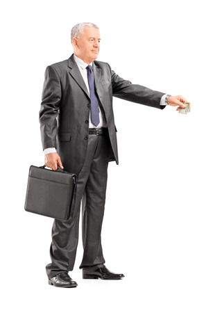 Full length portrait of a mature businessman giving money to someone isolated on white background photo