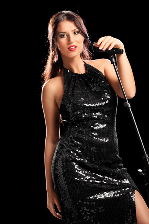 Beautiful female singer posing with microphone on black background