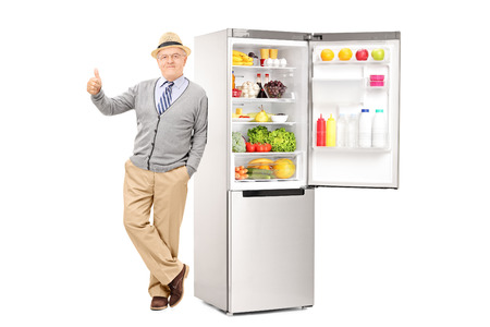 posing  agree: Senior leaning on a fridge and giving thumb up isolated on white background Stock Photo
