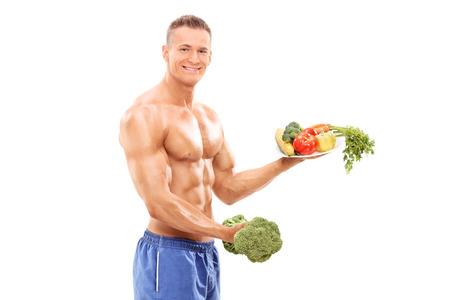 expresion corporal: Bodybuilder con una mancuerna br�coli y un plato lleno de verduras aislados sobre fondo blanco
