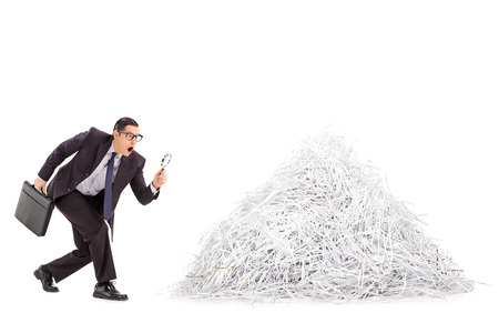shredding: Businessman examining a pile of shredded paper through a magnifying glass isolated on white background