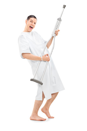 crutch: Full length portrait of a silly patient playing on a crutch and dancing isolated on white background