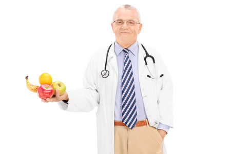 Mature doctor holding a bunch of fruits isolated on white background photo
