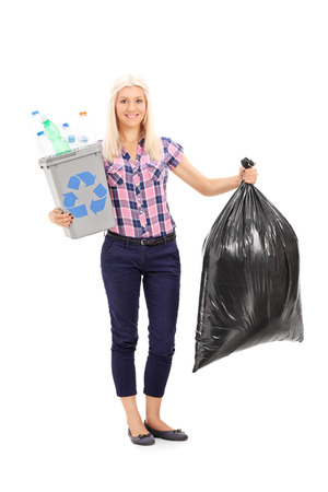 Full length portrait of a woman holding a recycle bin and a trash bag isolated on white background Stock Photo