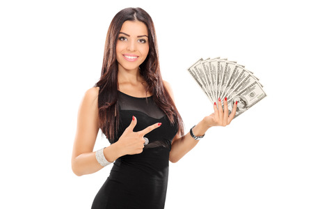 cash on hand: Woman pointing towards a stack of money with her finger isolated on white background