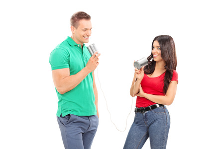 string together: Young couple talking through a tin can phone isolated on white background