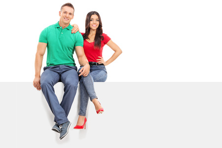 blank billboard: Handsome young couple sitting on a blank panel isolated on white background
