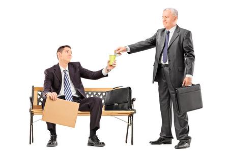 generoso: Hombre de negocios maduro que da un poco de dinero a un mendigo aislado en fondo blanco Foto de archivo