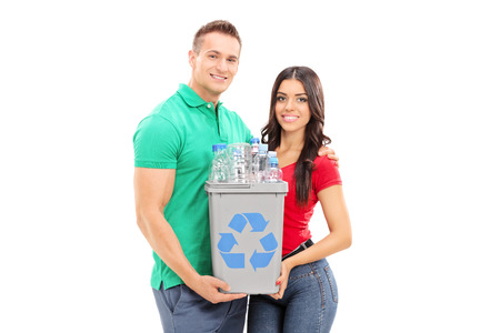 Young couple holding a recycle bin isolated on white background photo