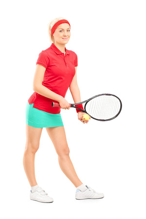 Full length portrait of a female tennis player preparing to serve isolated on white background photo