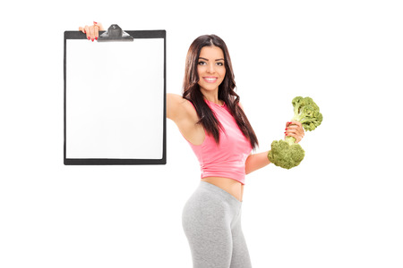Woman holding a broccoli dumbbell and clipboard isolated on white background photo