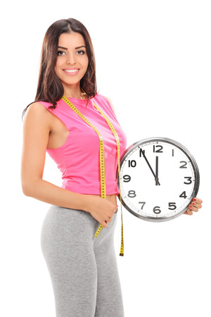 Young woman holding a big wall clock isolated on white background photo
