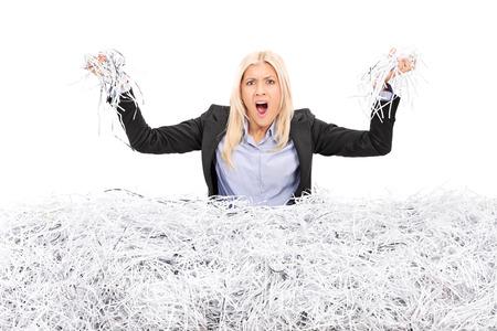Boos zakenvrouw in een stapel van geraspte papier op een witte achtergrond