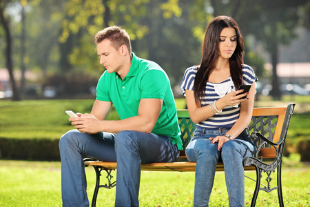 conflicted: Conflicted couple not talking to each other seated on a wooden bench in park