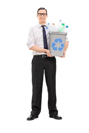 papelera de reciclaje: Retrato de cuerpo entero de un hombre joven con una papelera de reciclaje llena de botellas de pl�stico aisladas sobre fondo blanco
