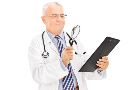 Mature doctor examining a document through a magnifying glass isolated on white background photo